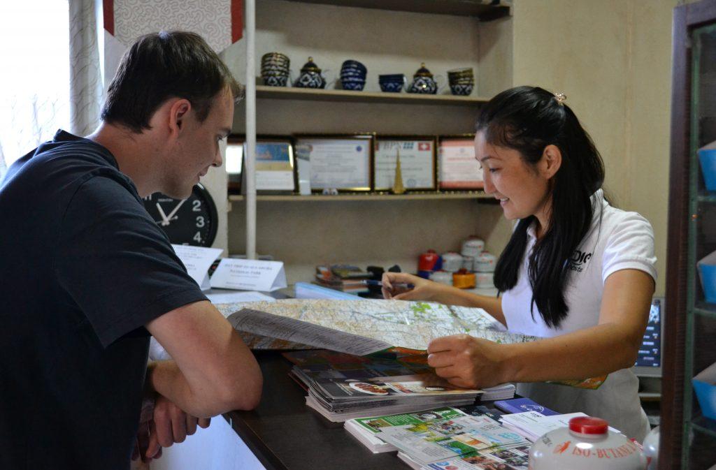 Helping guest at Apple Hostel Bishkek